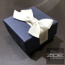 Gyűrűs vagy fülbevalós doboz , kék színű matt alap, ekrü színű szatén masnival